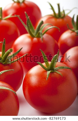 Close up of red small tomatoes isolated over white.