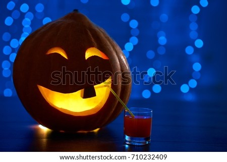 Close up of red smiling pumpkin with one tooth and big eyes, decoration prepared for Halloween smiling and drinking cocktail at party. Dark blue background with lights. Autumn holiday. #710232409
