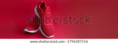 Close-up of red sneakers on bright backdrop. Sport footwear for running and fitness. Amazing pair of shoes. Active lifestyle. Nice texture with white sole and laces Foto stock ©