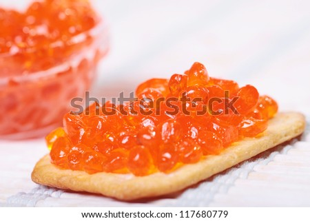 Close up of red tasty caviar in a glass jar with cracker