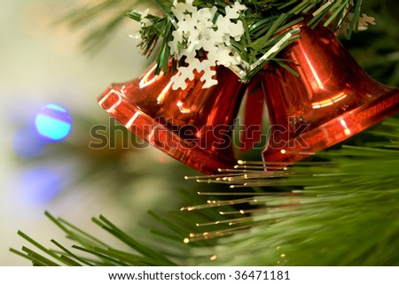 Close-up of red toy bells hanging on green spruce branch decorated with paper snowflake #36471181