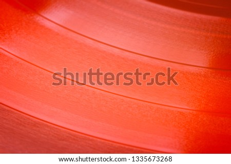 Close up of red vinyl surface. Red vinyl record texture background. Close up of vinyl LP record showing grooves