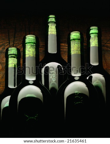 Close up of red wine bottles on a wooden background