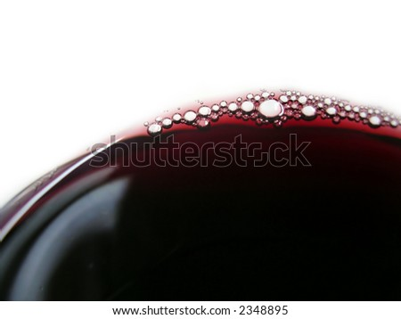 Close-up of red wine bubles in a transparent glass.