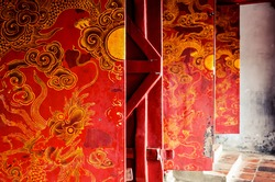 Close up of red wooden temple doors with traditional asian golden yellow art decoration engravings.