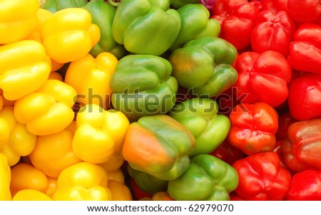 close up of red, yellow and green peppers on market stand