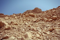 Close-up of reddish rocks in the desert (Ein Gedi - Nahal Arugot - Israel). Blue sky in the background. Selective Focus.