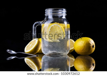 Close up of refreshing healthy lemonade in glass jar and fresh sliced lemons with black background