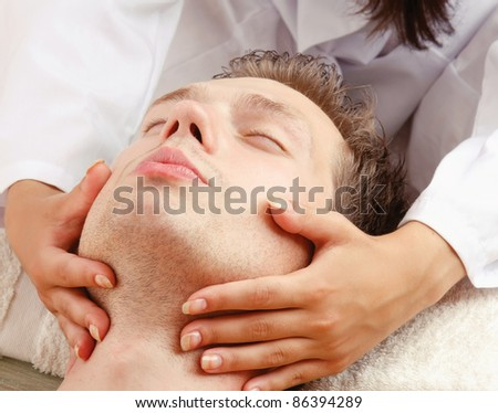 Close-up of relaxed young man getting facial massage isolated