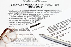 close up of resume form on white with employment contract. Note: all information are fiction.