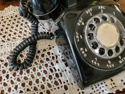 close up of retro rotary black telephone on old-fashioned lace doily