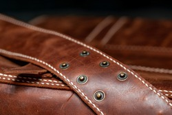 Close-up of retro style brown leather messenger bag with rivet straps.