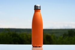 Close-up of reusable steel eco thermo water bottle with silver cap, lush lava color, standing on glass desk, on background of cyan sky.