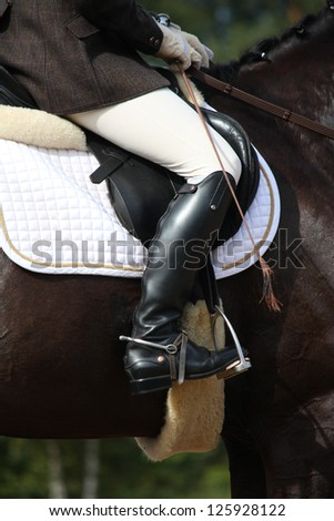 Close up of rider on horse during dressage competition