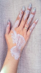 Close up of right hand of a young Asian Muslim woman bride to be, painted with silver color henna for wedding day. Diamond ring on finger. Asian culture.