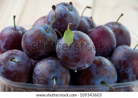 Close-up of ripe plums in a plastic container