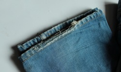 Close up of ripped, worn denim jeans