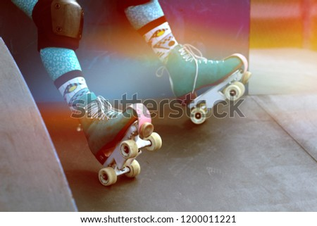 Close up of roller skates at on a skater sitting on a ramp at the skate park, photo filtered to have a rainbow vintage look