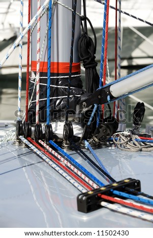 Close up of ropes and equipment on the side of a mast on a new yacht.