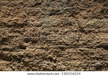 Close-up of rough plaster on an old wall forming a quaint background at Caceres. A cute and charming town with a fully preserved medieval city center in western Spain.