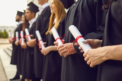Close up of row of students in black robes standing with traditional rolled up diplomas in hands at graduation ceremony. Happy graduates with honors in black togas celebrating their milestone event