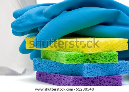 Close up of rubber gloves and sponges over white background