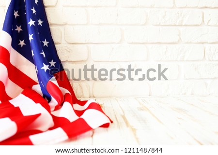 Close up of ruffled American flag over lofty white brick wall with a lot of copy space. Patriotic background for national holidays in United States of America. Stars and stripes. #1211487844