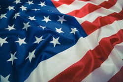 Close up of ruffled American flag. Satin texture curved flag of USA. Memorial Day or 4th of July. Banner, freedom concept