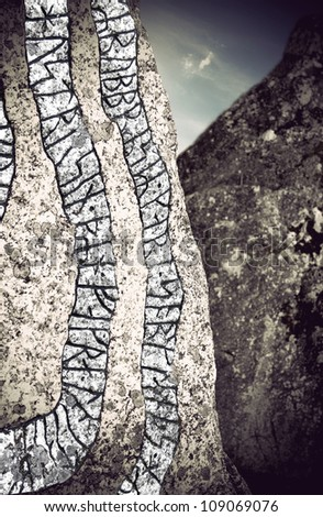Close up of rune stone with ancient characters on granite