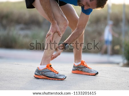 close up of runner touching painful twisted or broken ankle shin or calf athlete runner training accident sport running ankle sprain concept