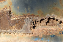 Close up of rust damage to metal surface. Photo shows corrosion concept.