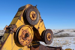 close up of rusted old pulley of an abandoned yellow combine with blue skies and snow covered hills