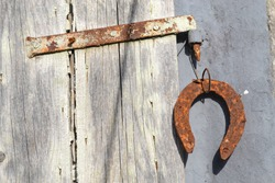 Close up of rusty bolt with horseshoe on old wooden window