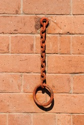 Close Up of Rusty Iron Ring and Chain against Brick Wall