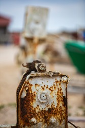 Close up of rusty winches used for pulling fishing boats out of the water with boats and ramps in the background near a fishermen village on the Romania litoral of the Black Sea
