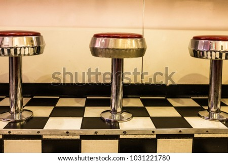 Close up of 50s diner chrome and red stools on black and white checkerboard tiled floor