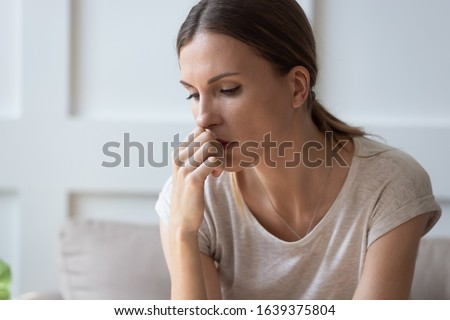 Close up of sad pensive millennial woman sit alone thinking about relationships personal problems, upset thoughtful young female lost in thoughts feel lonely depressed pondering or mourning at home