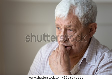 Close up of sad thoughtful old grandfather look in distance feel lonely and depressed, upset pensive mournful senior man husband thinking pondering missing passed wife, elderly solitude concept