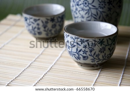 Close up of Sake cup on bamboo pad.