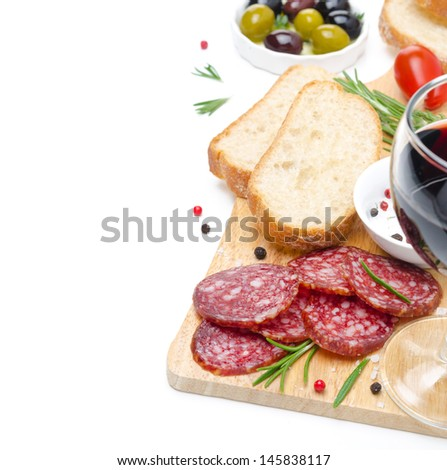 close-up of salami, ciabatta, olives and glass of wine on a wooden board isolated on white