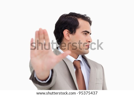 Close up of salesman signalizing stop against a white background