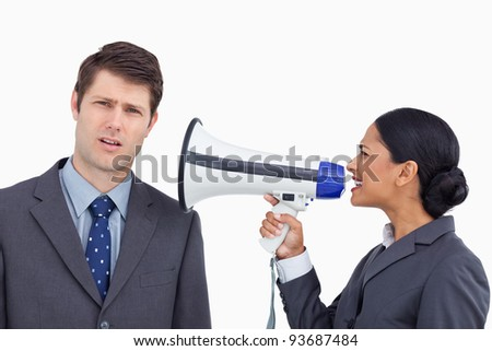 Close up of saleswoman with megaphone yelling at colleague against a white background