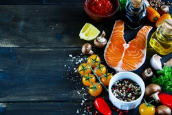 Close up of salmon steak with fresh ingredients for tasty cooking on rustic wooden background, selective focus, banner. Healthy food concept.