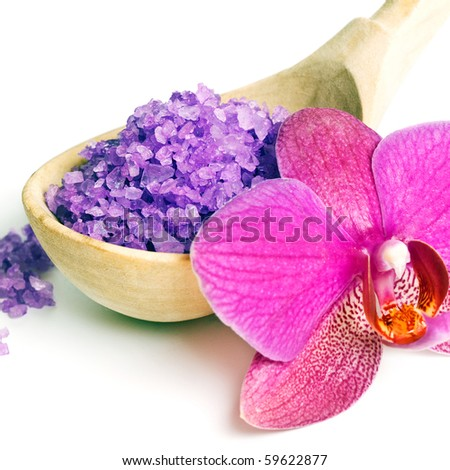 Close up of salt crystals in a wooden scoop and orchid on white