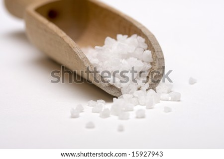 Close up of salt crystals in a wooden scoop on white