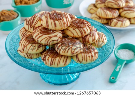 Close up of salted caramel thumbprint cookies drizzled with chocolate sitting on decorative blue glass pastry stand and additional cookies on white plate surrounded by ingredients in blue utensils
