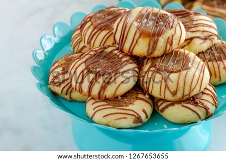 Close up of salted caramel thumbprint cookies drizzled with milk chocolate sitting on bright blue pastry stand with copy space on left