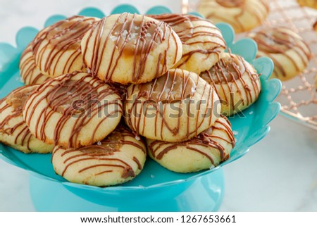 Close up of salted caramel thumbprint cookies drizzled with milk chocolate sitting on bright blue pastry stand