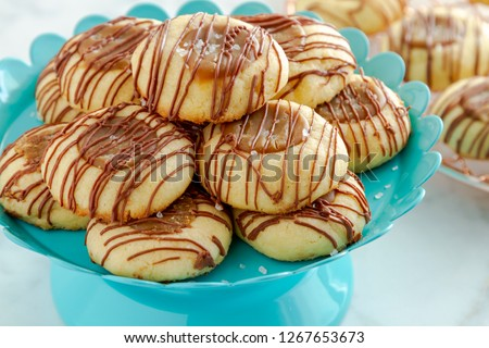 Close up of salted caramel thumbprint cookies drizzled with milk chocolate sitting on bright blue pastry stand and copper cooling rack in background