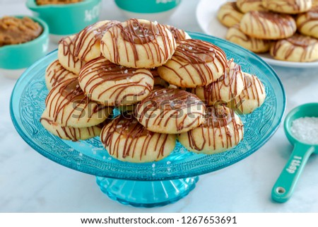 Close up of salted caramel thumbprint cookies drizzled with milk chocolate sitting on decorative blue glass pasty stand and additional cookies on white plate surrounded by ingredients